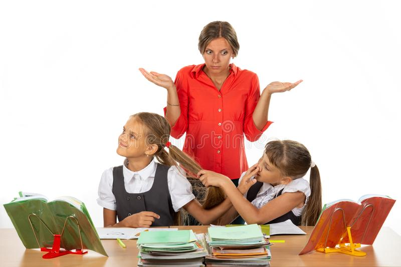 The girls in the lesson made a squabble, the teacher does not know what to do with them royalty free stock photos