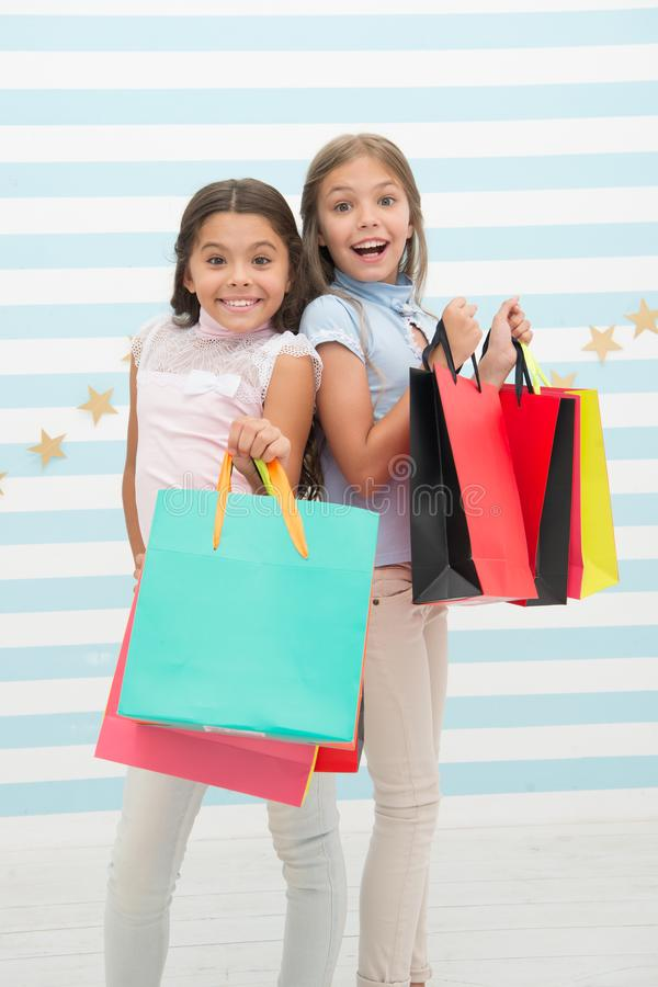 Girls like shopping. Kids happy small girls hold shopping bags. Enjoy shopping with best friend or sister. Girlish. Happiness. Kids happy carry bunch packages royalty free stock image