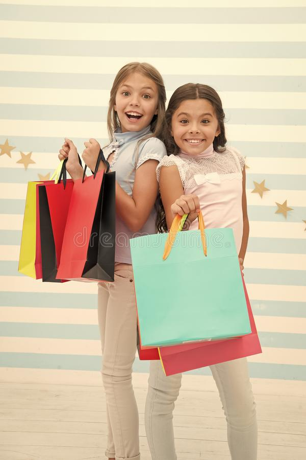 Girls like shopping. Kids happy small girls hold shopping bags. Enjoy shopping with best friend or sister. Girlish. Happiness. Kids happy carry bunch packages stock photography