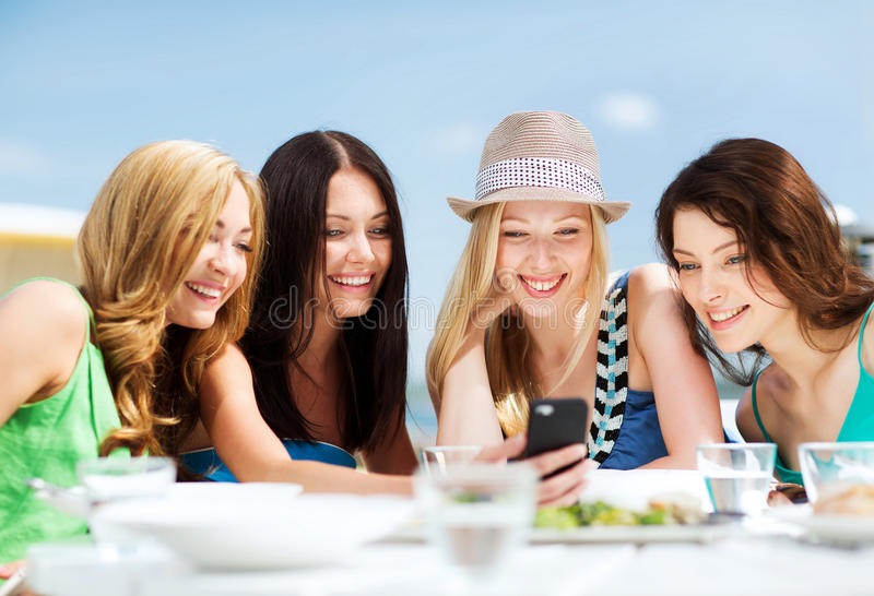 Girls Looking At Smartphone In Cafe On The Beach Royalty Free Stock Images