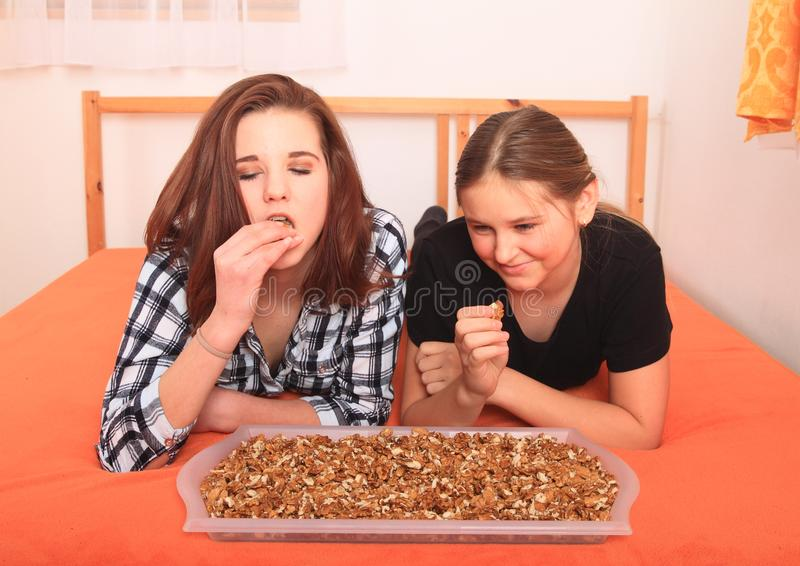 Girls lying on bed and eating nuts stock photography