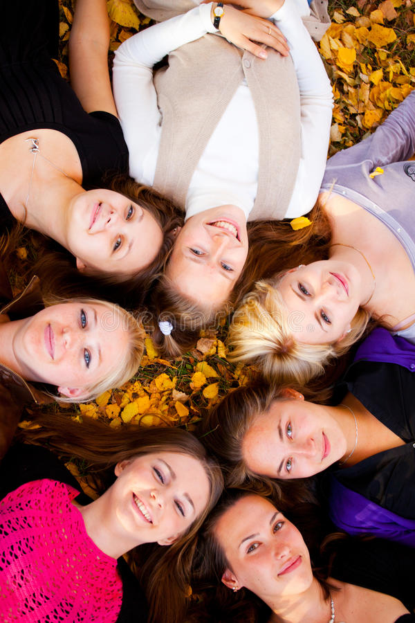 Girls lying on the grass. Young beautiful girls lying on the grass royalty free stock photo