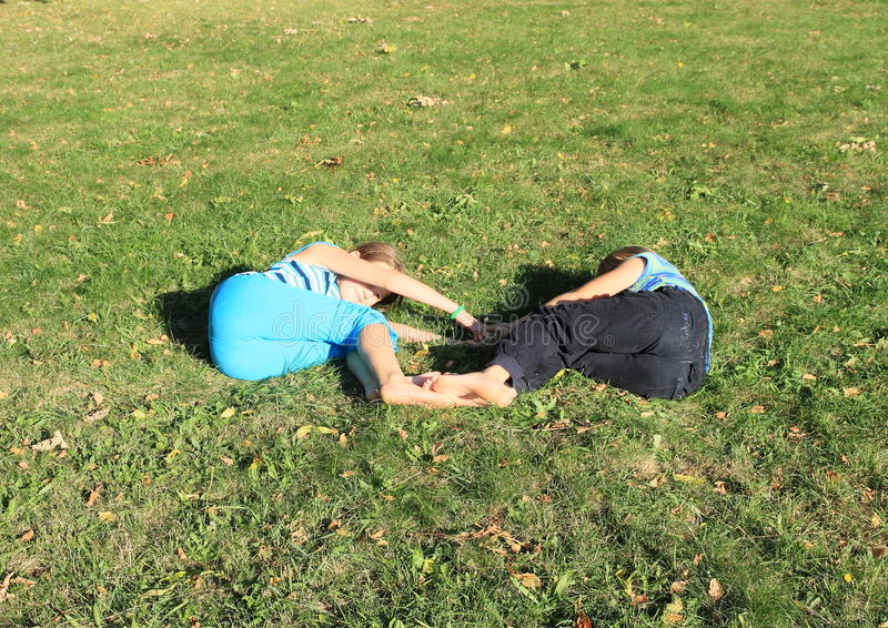 Girls lying on meadow stock images