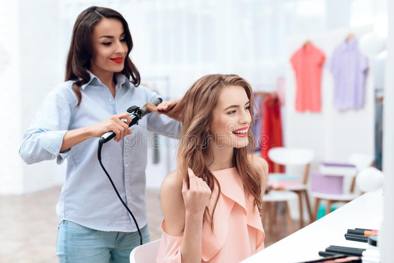 Girls make hair styling in the showroom. Girls make hair styling in the showroom. Two beautiful girls have fun and smile royalty free stock photography