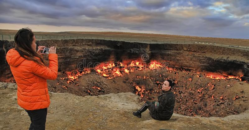 Girls make a photo on the background of the burning crater stock photos