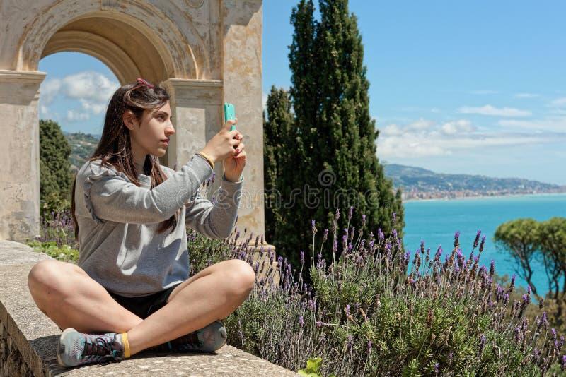 Girls make photo by phone in the riviera coast, liguria, italy stock photos