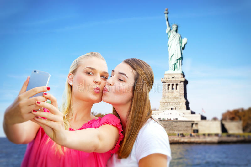 Girls making a selfie in in New York. Girlfriends with smart phone in the USA, in background the statue of liberty stock images