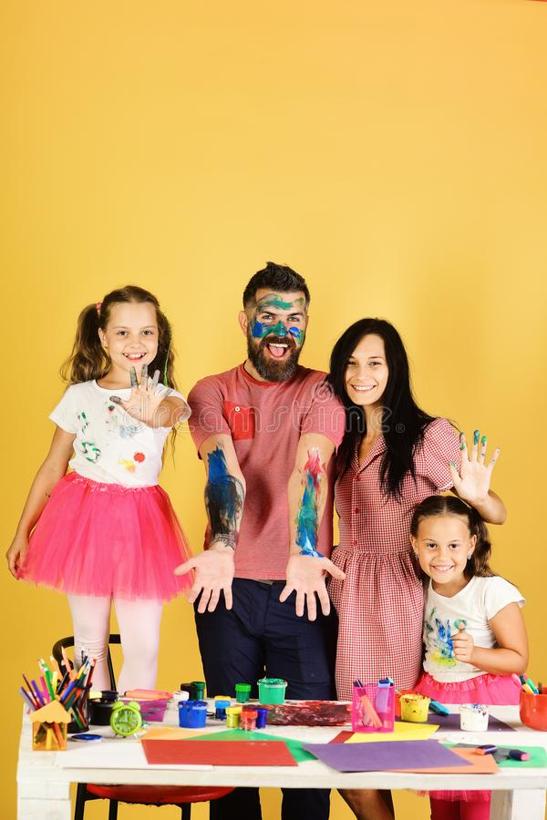 Girls, man and woman with happy faces by art desk, copy space. Artists create artwork on guys body. Family leisure time royalty free stock photos