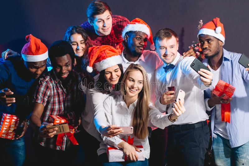 Girls and guys in Santa hats doing selfie at party. Christmas, new year concept stock photo