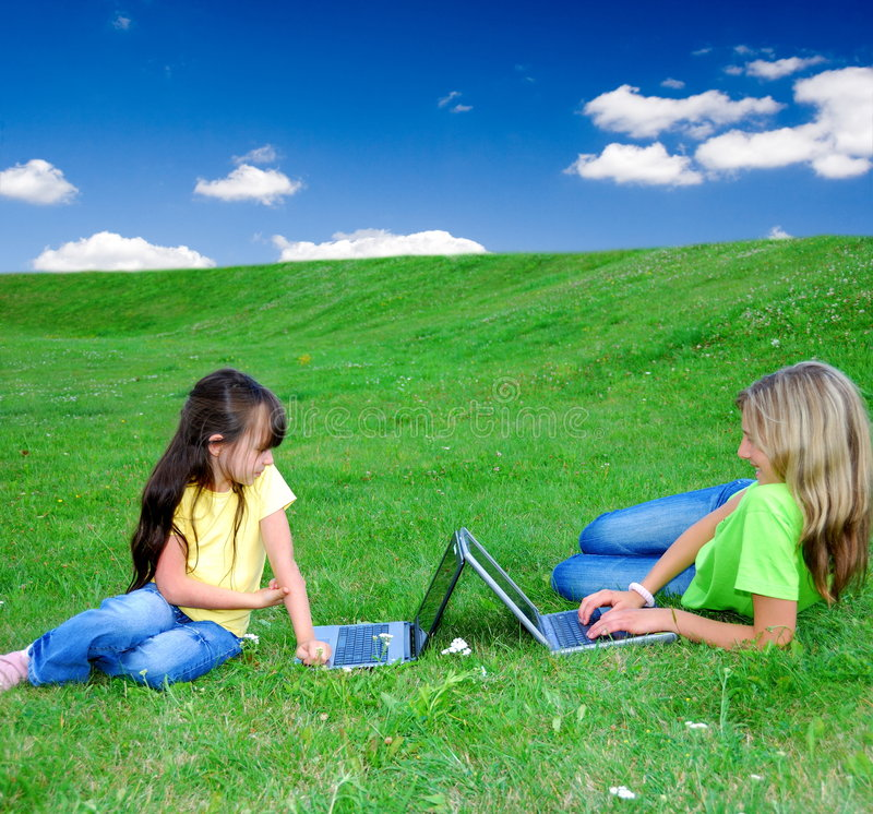 Girls in meadow with laptops stock photo