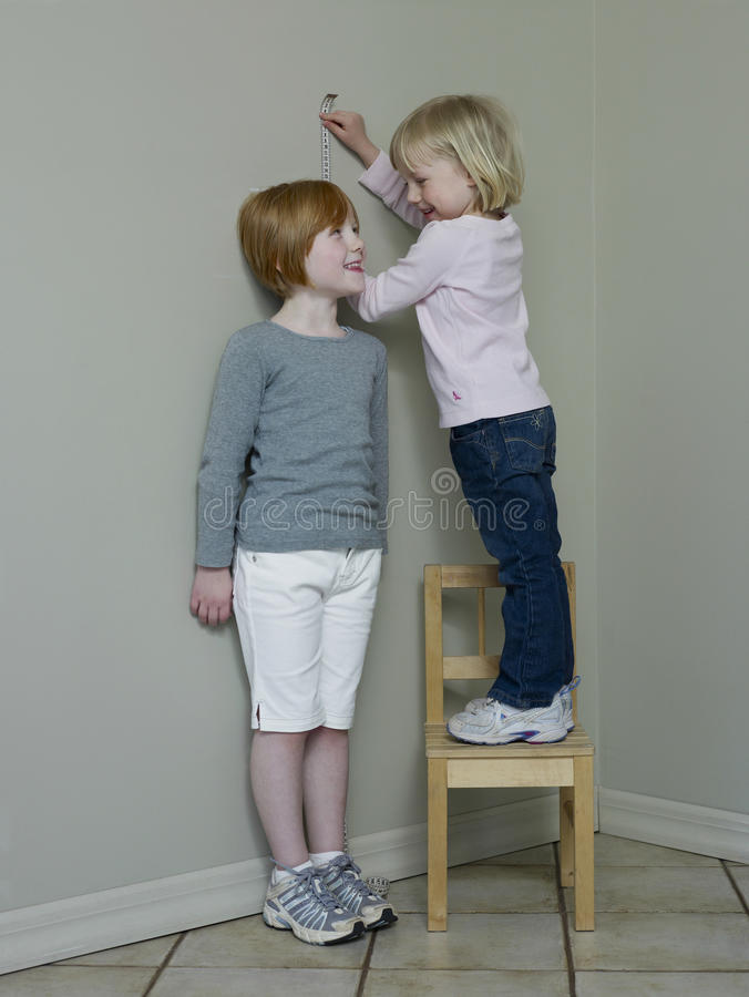 Girls Measuring Height Against Wall Stock Photo - Image of ...