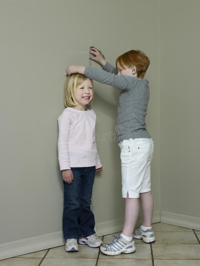 Download Girls Measuring Height Difference Against Wall Stock Photo - Image: 33912120