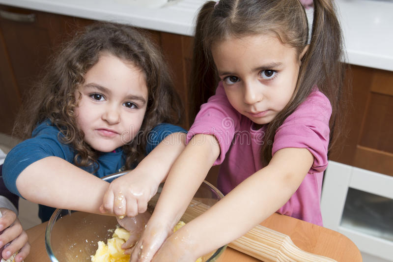 Girls mixing dough with hands stock images