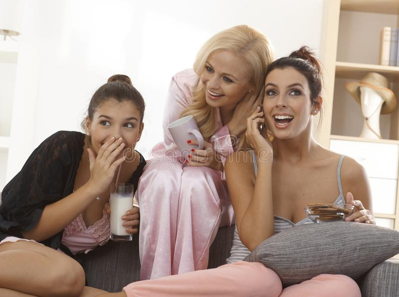 Girls on mobilephone. Three girls in pyjamas at home listening as one talking to boyfriend, smiling elfish stock images