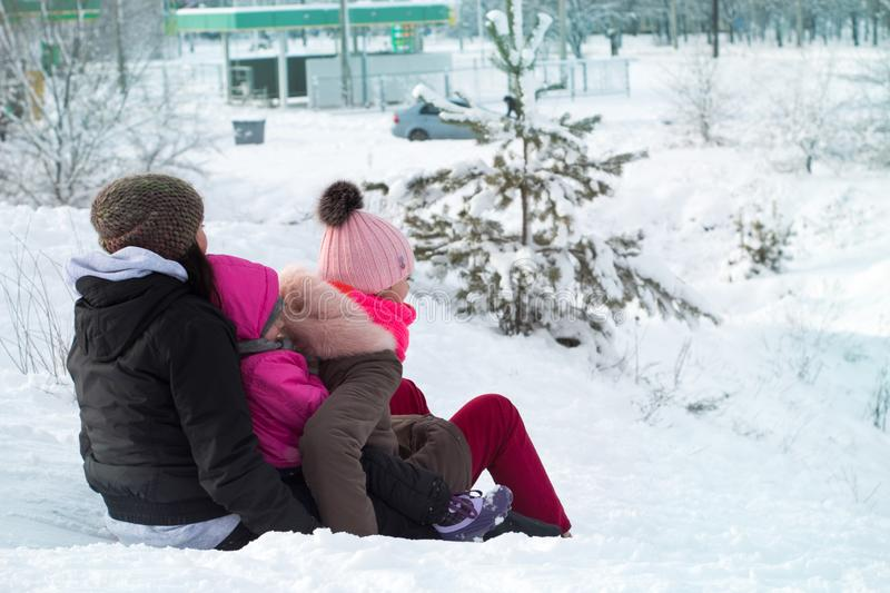 girls and mom slide down the hill stock photos