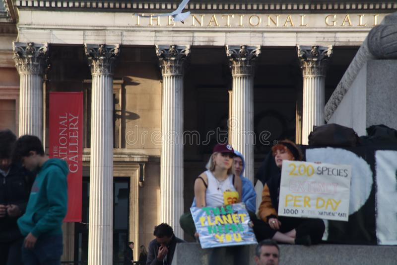 Girls On Nelson`s Column at Extinction Rebellion Protest. royalty free stock photos