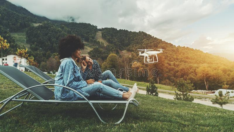 Girls outdoor are recording video for their vlogs using drone royalty free stock image