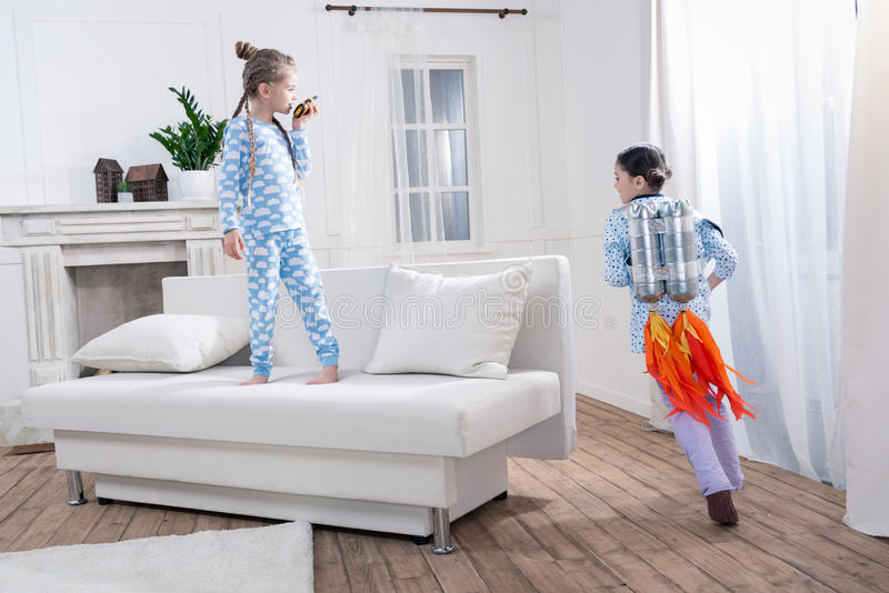 Girls in pajamas playing cosmonauts. At home stock images