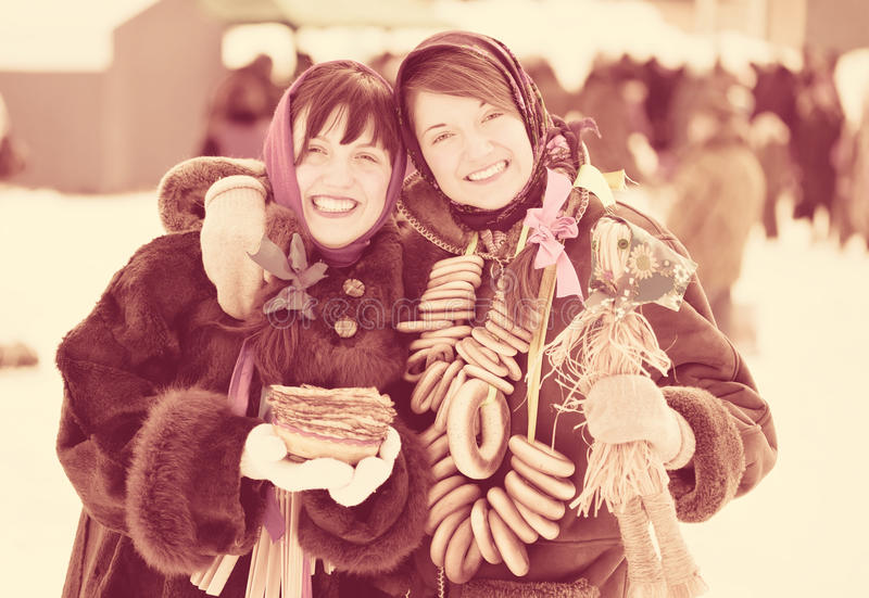 Girls with pancake and round cracknel during Shrovetide. Happy girls in russian traditional clothes with pancake and round cracknel during Shrovetide stock photography