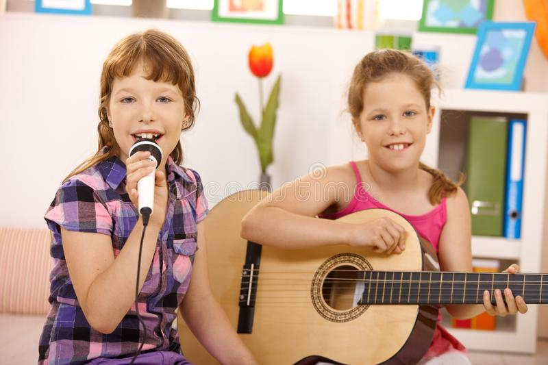 Girls performing music. Portrait of young girls performing music, singing and playing guitar, smiling at camera royalty free stock photo