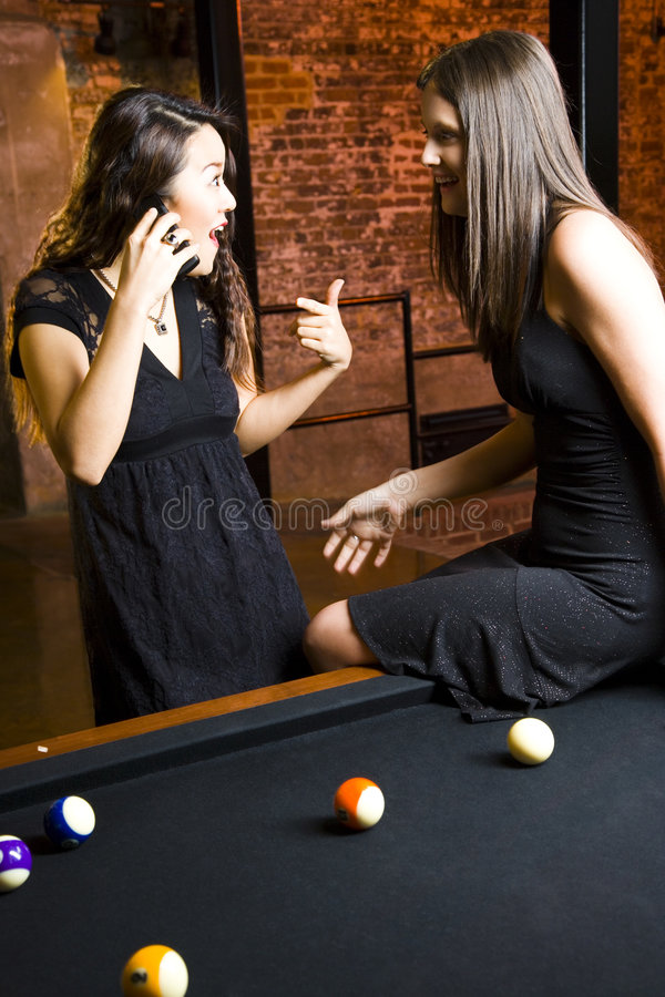 Girls on phone in poolroom. A view of an excited girl and her female friend standing at a pool table and talking on a cellphone royalty free stock images