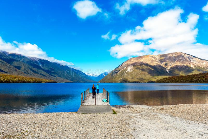 Girls on pier river Rotoiti, Nelson Lakes National Park, New Zealand.  stock images
