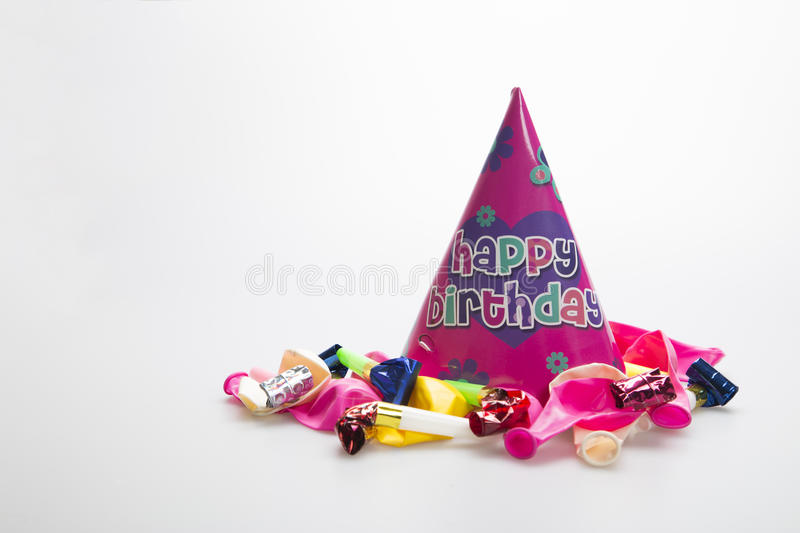 Girls pink birthday hat. Birthday party hat on white background with balloons and party blower stock photography