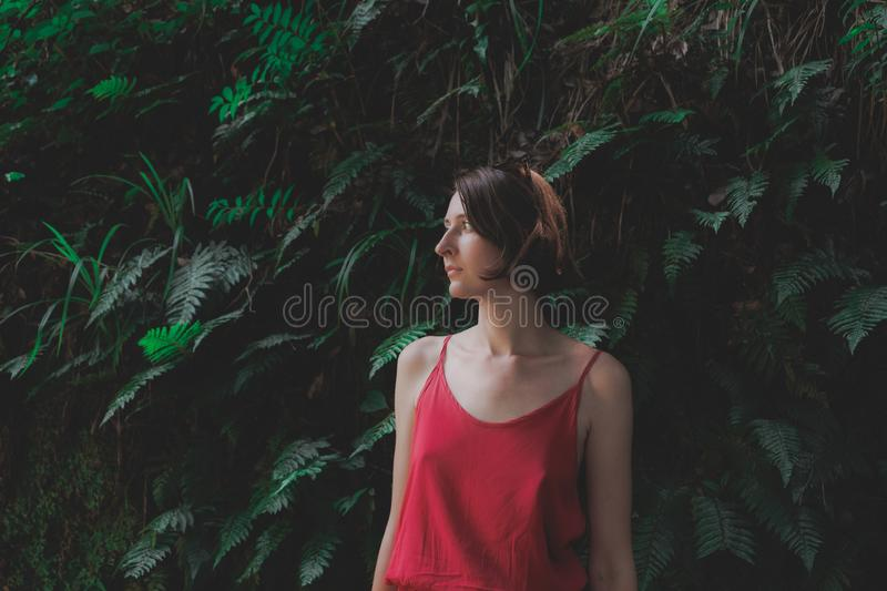 Girls and plants: portrait of a beautiful woman in red dress on natural green background. royalty free stock photography