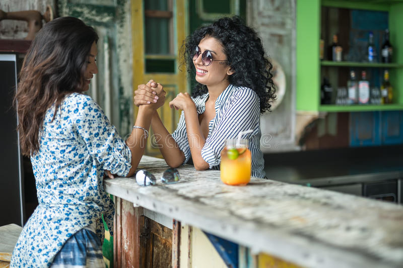 Girls play arm wrestling. Joyful smiling girls in the bar outdoors. Women play arm wrestling on the wooden bar rack. They wear light shirts with patterns, shorts stock photos