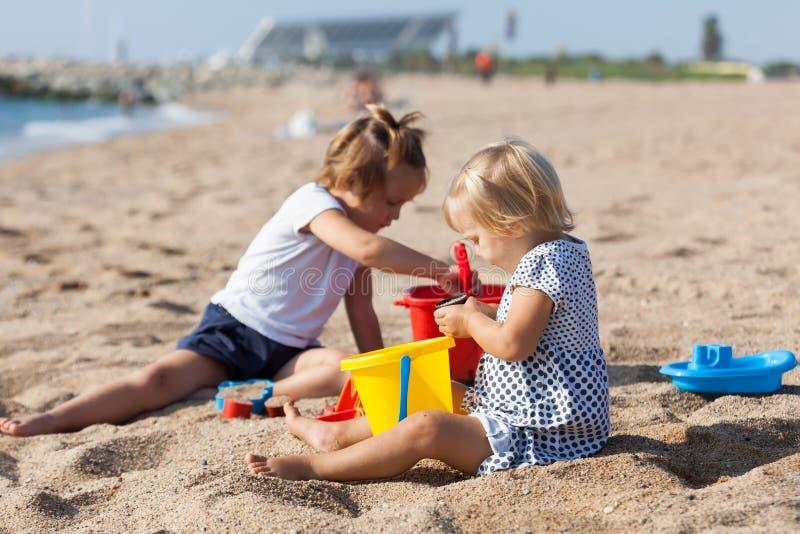 Girls play on the beach stock photos