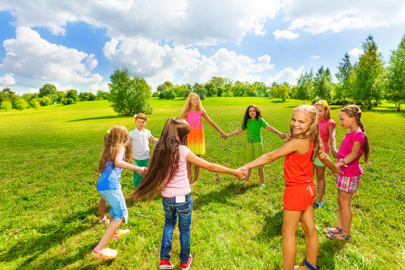 Girls play in the park. Large group of happy girls play roundelay and stand in circle in the park on the green field royalty free stock photo