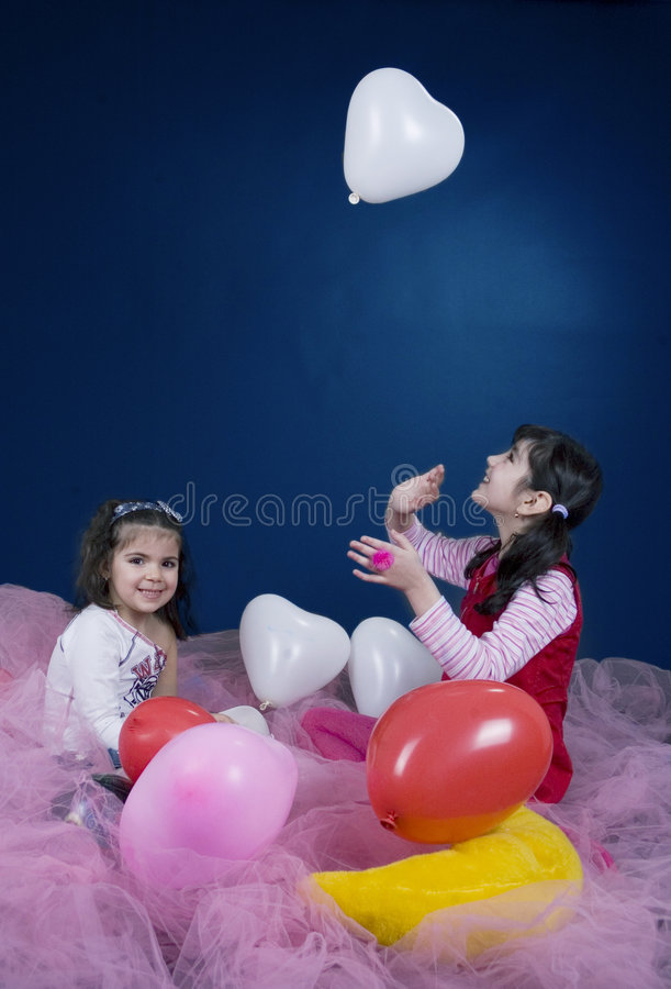 Girls playing with balloons royalty free stock images