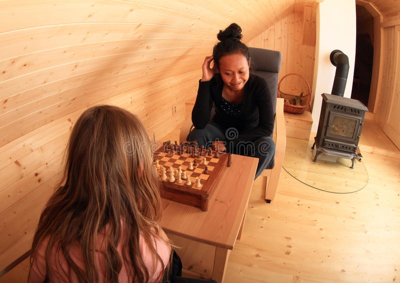 Girls playing chess in attic. Two girls - blond Caucasian kid and young exotic Papuan women sitting on armchairs and playing chess in wooden attic room with royalty free stock photography