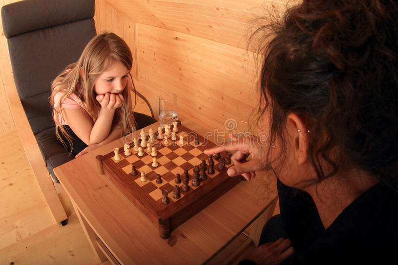 Girls playing chess - ready to move. Two girls - blond Caucasian kid and young exotic Papuan women ready to move a chessman - sitting on armchairs and playing stock image