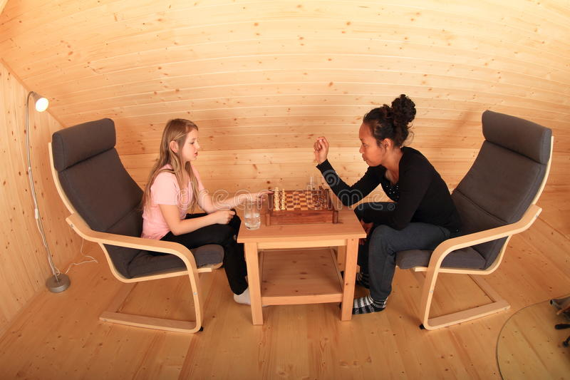 Girls playing chess. Two girls - blond Caucasian kid and young exotic Papuan women sitting on armchairs and playing chess in wooden attic room royalty free stock images