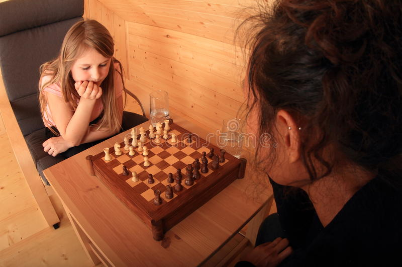Girls playing chess. Two girls - blond Caucasian kid and young exotic Papuan women sitting on armchairs and playing chess in wooden attic room stock image