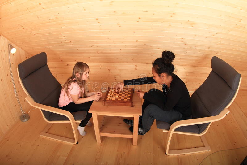 Girls playing draughts. Two concentrated girls sitting on armchairs - blond Caucasian kid and young exotic Papuan women playing draughts or checkers on royalty free stock photos