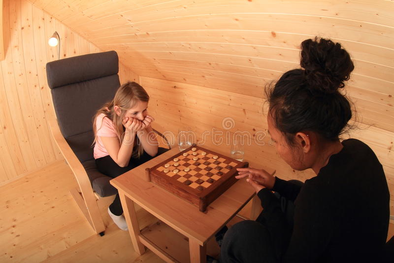 Girls playing draughts. Two concentrated girls sitting on armchairs - blond Caucasian kid and young exotic Papuan women playing draughts or checkers on stock images