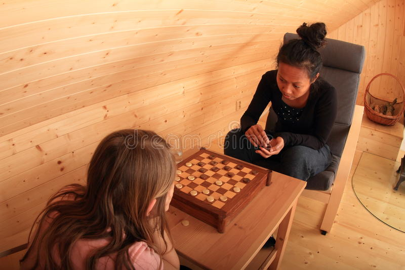 Girls playing draughts. Two concentrated girls sitting on armchairs - blond Caucasian kid and young exotic Papuan women playing draughts or checkers on stock image