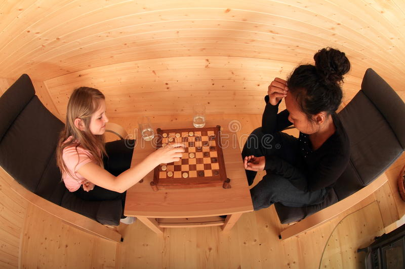 Girls playing draughts. Two concentrated girls sitting on armchairs - blond Caucasian kid and young exotic Papuan women playing draughts or checkers on royalty free stock photo