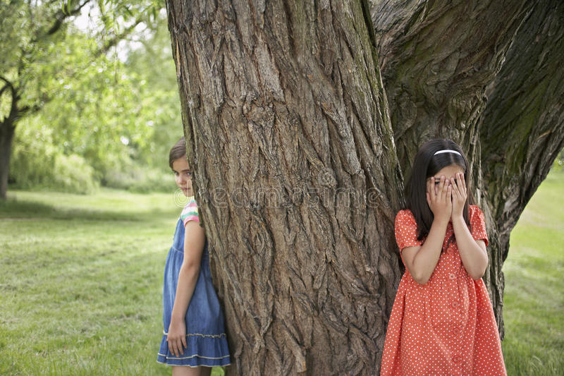 Girls Playing Hide And Seek By Tree. Two girls playing hide and seek by tree in park royalty free stock photos