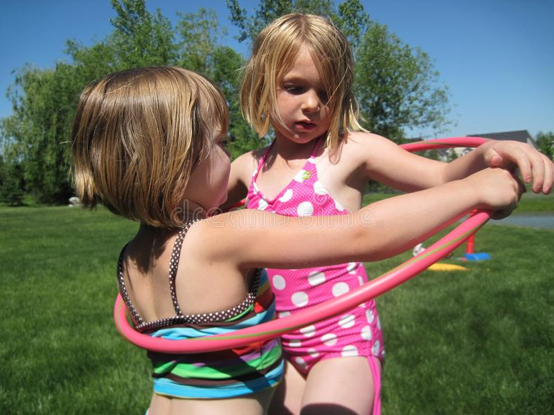 Girls playing with hoola hoop in the summer. in the grass royalty free stock photos