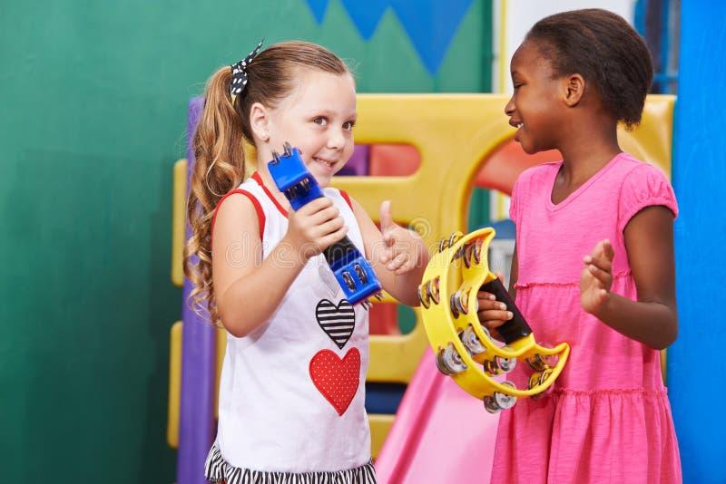 Girls playing music with tambourine. Two girls playing music with tambourine in a kindergarten royalty free stock photography