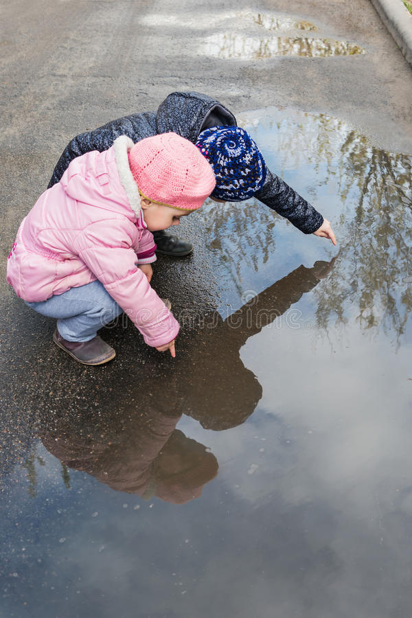 Girls playing in a puddle royalty free stock image