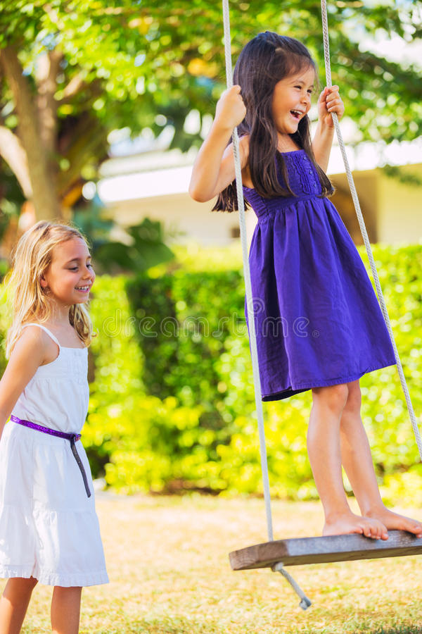 Girls Playing on Swing royalty free stock images