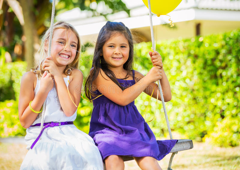 Girls Playing on Swing stock images
