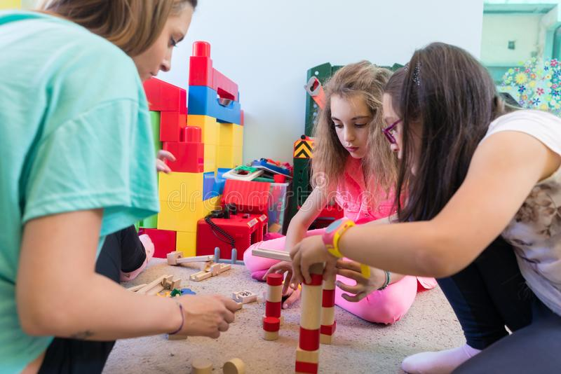 Girls playing together with wooden toy blocks on the floor durin royalty free stock photo