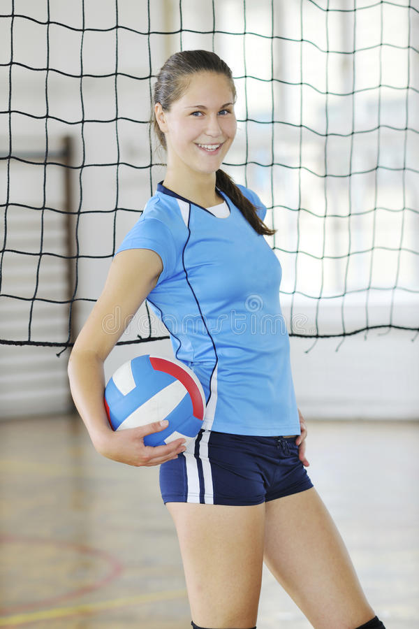 Girls playing volleyball indoor game. Volleyball game sport with group of girls indoor in sport arena stock photo