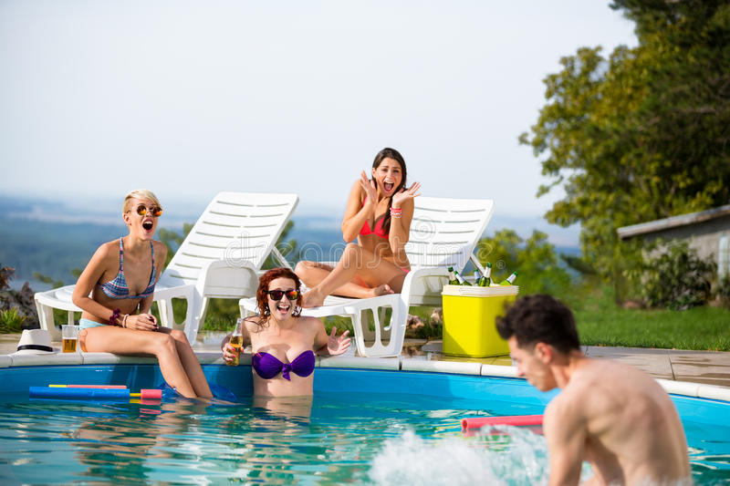 Girls at pool surprised by their male friend in water. Young girls at swimming pool surprised by their male friend in water stock photos