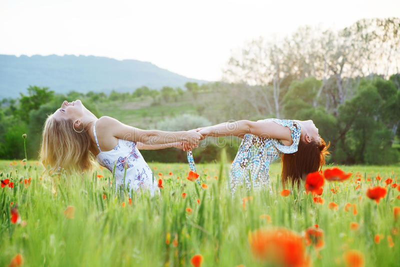Girls in poppy field stock images